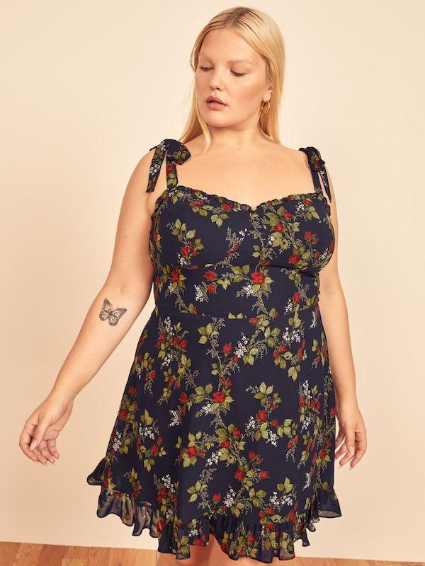 A model wearing a plus-size floral mini dress.