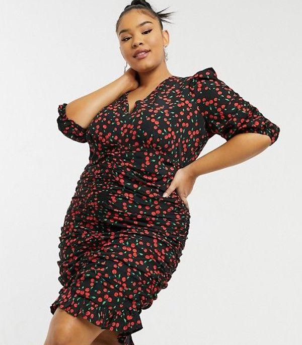 A model wearing a plus-size fruit print dress.