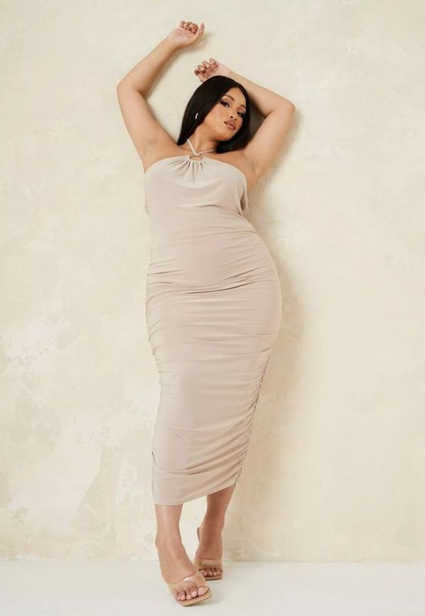A model wearing a plus-size halter dress in beige.
