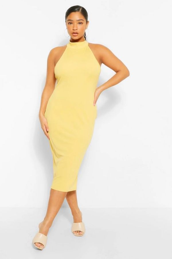 A model wearing a plus-size halter dress in yellow.