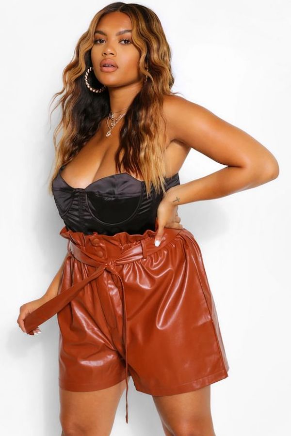 A model wearing plus-size leather shorts in brown.