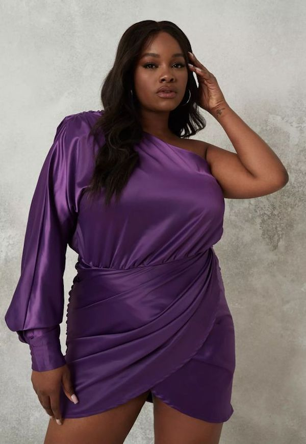 A model wearing a plus-size one-shoulder dress in purple.