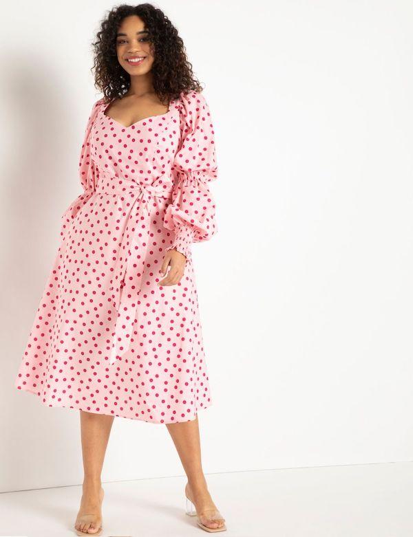 A model wearing a plus-size polka dot dress in pink.