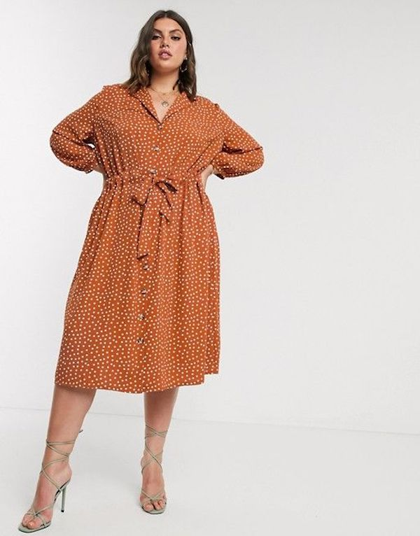 A model wearing a plus-size polka dot dress in burnt orange.