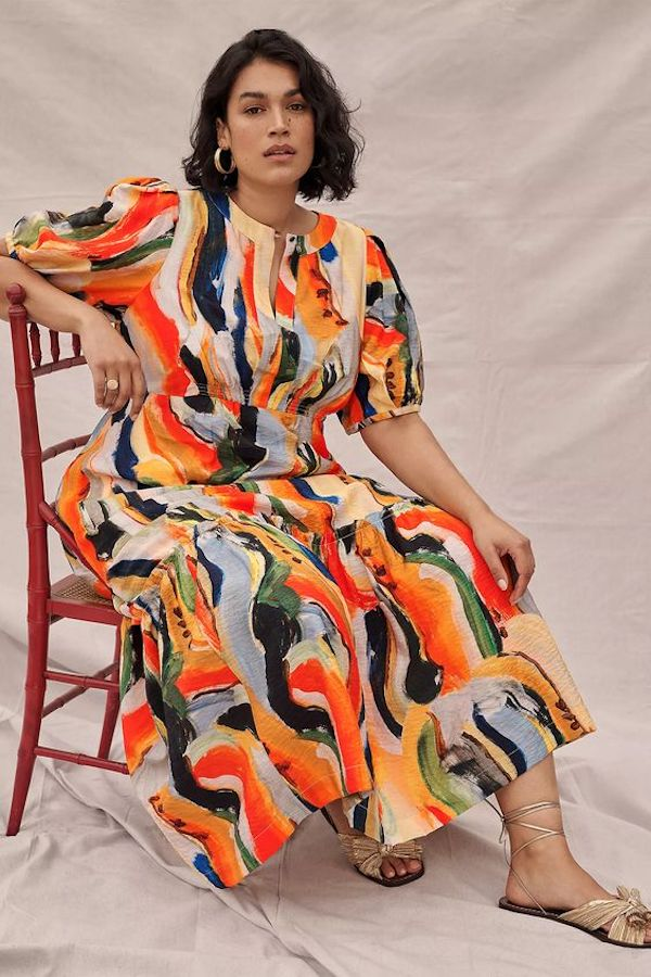 A model wearing a plus-size puff-sleeve dress in orange and blue.