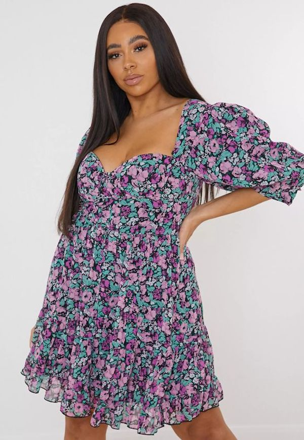 A model wearing a plus-size puff-sleeve dress in floral print.