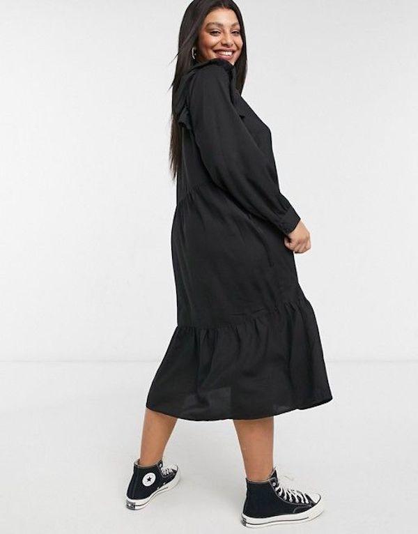 A model wearing a plus-size ruffle dress in black.