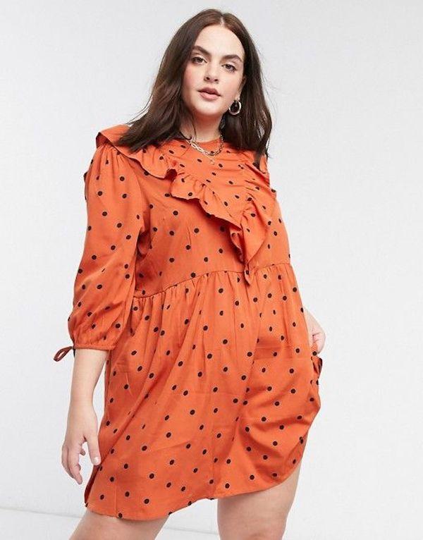 A model wearing a plus-size ruffle dress in orange.