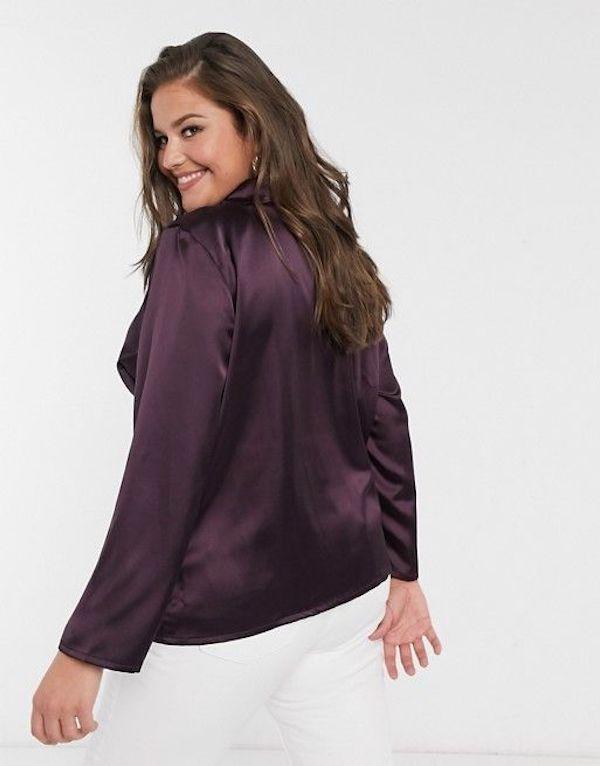 A model wearing a plus-size satin button down in dark purple.