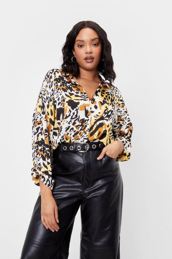 A model wearing a plus-size satin button down in animal print.