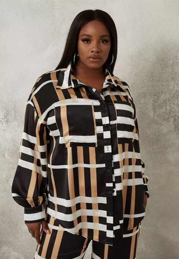 A model wearing a plus-size satin button down in brown and black stripe.