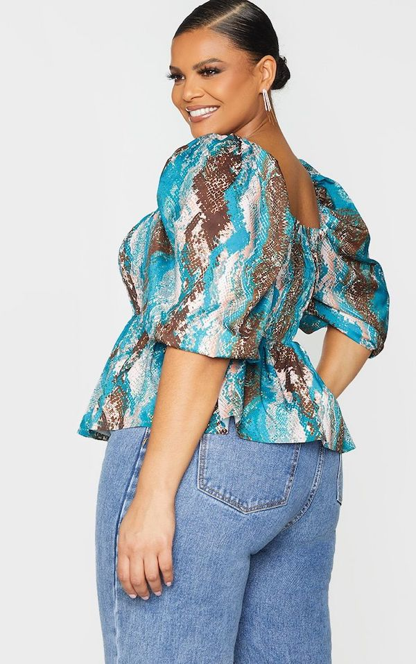 A model wearing a plus-size shirred top.