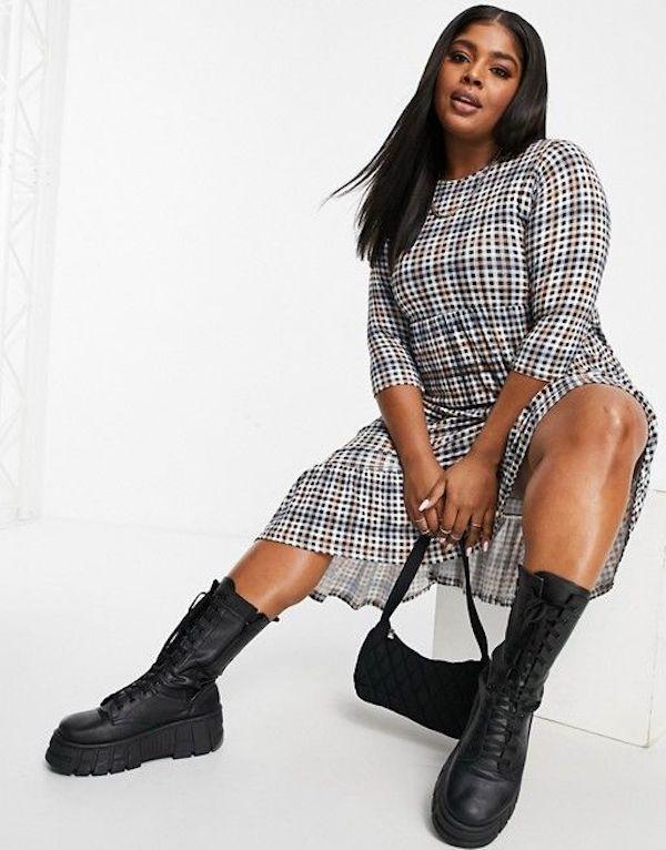 A model wearing a plus-size plaid dress.