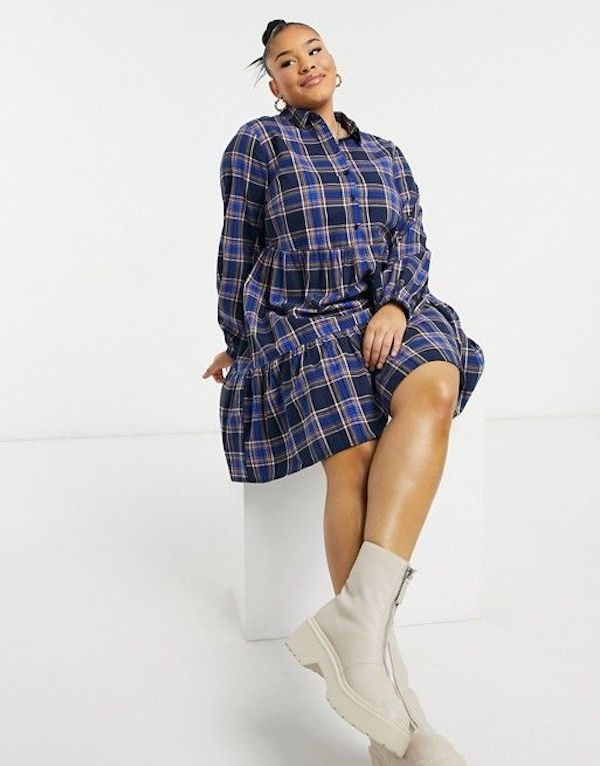 A model wearing a plus-size plaid dress.