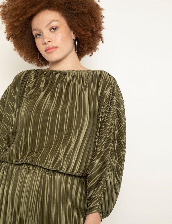 A model wearing a green plisse top from ELOQUII.