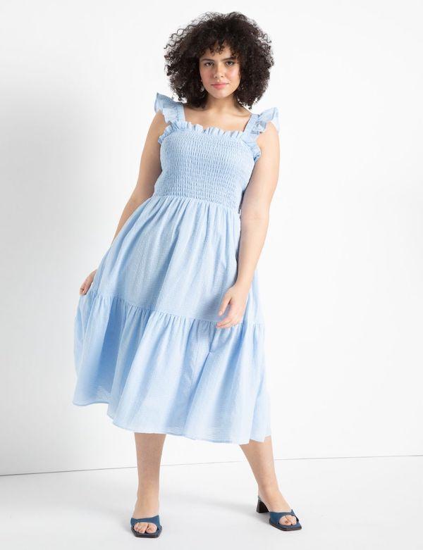 A model wearing a plus-size shirred dress.