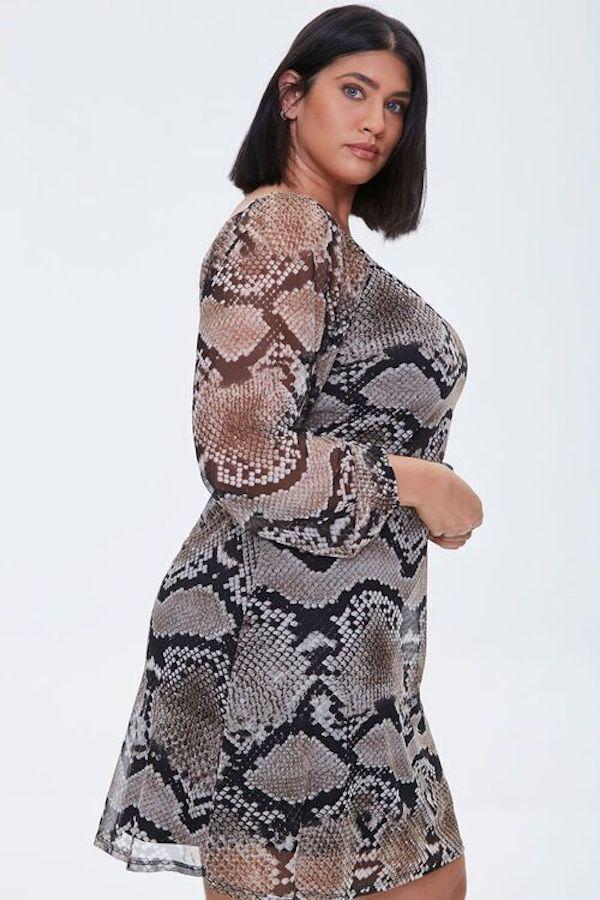 A model wearing a plus-size snake print dress.