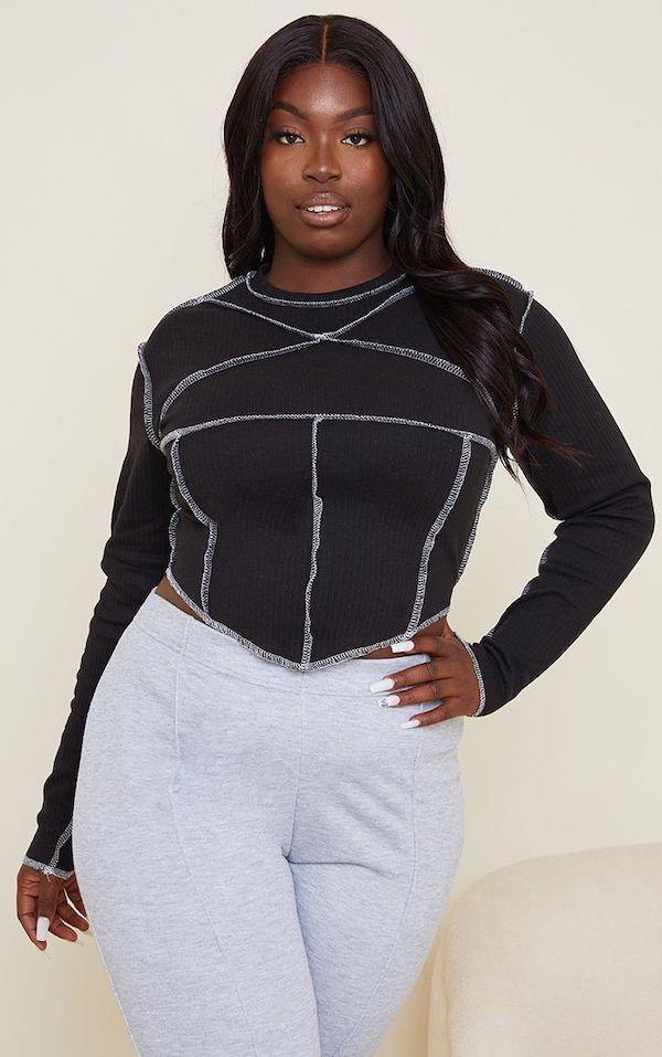 A model wearing a plus-size corset tee.