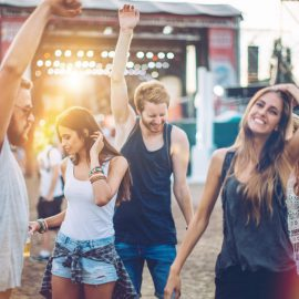 Young people having fun at concert.  Stage in background. Summertime, evening. Caucasian ethnicity.