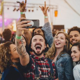 Group of young adult friends are taking a group selfie on a smartphone while they are at a festival.