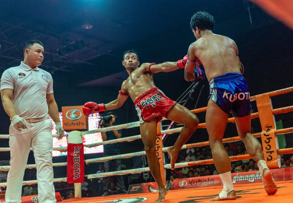 Cambodian kick boxer swings for his Thai opponent
