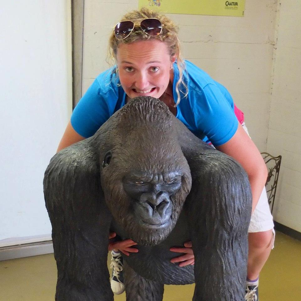Photo of Bea straddling a gorilla, taken in Cabarceno, Spain.
