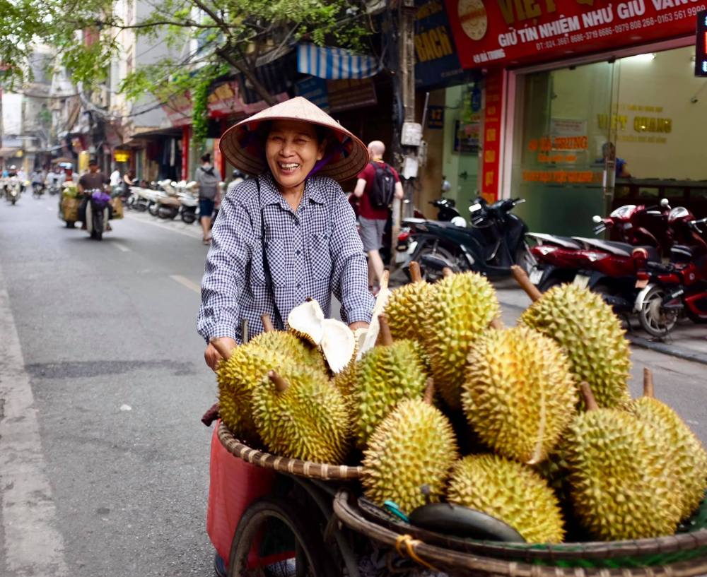 Photo of a lady street vendor pushing her large cart of durian