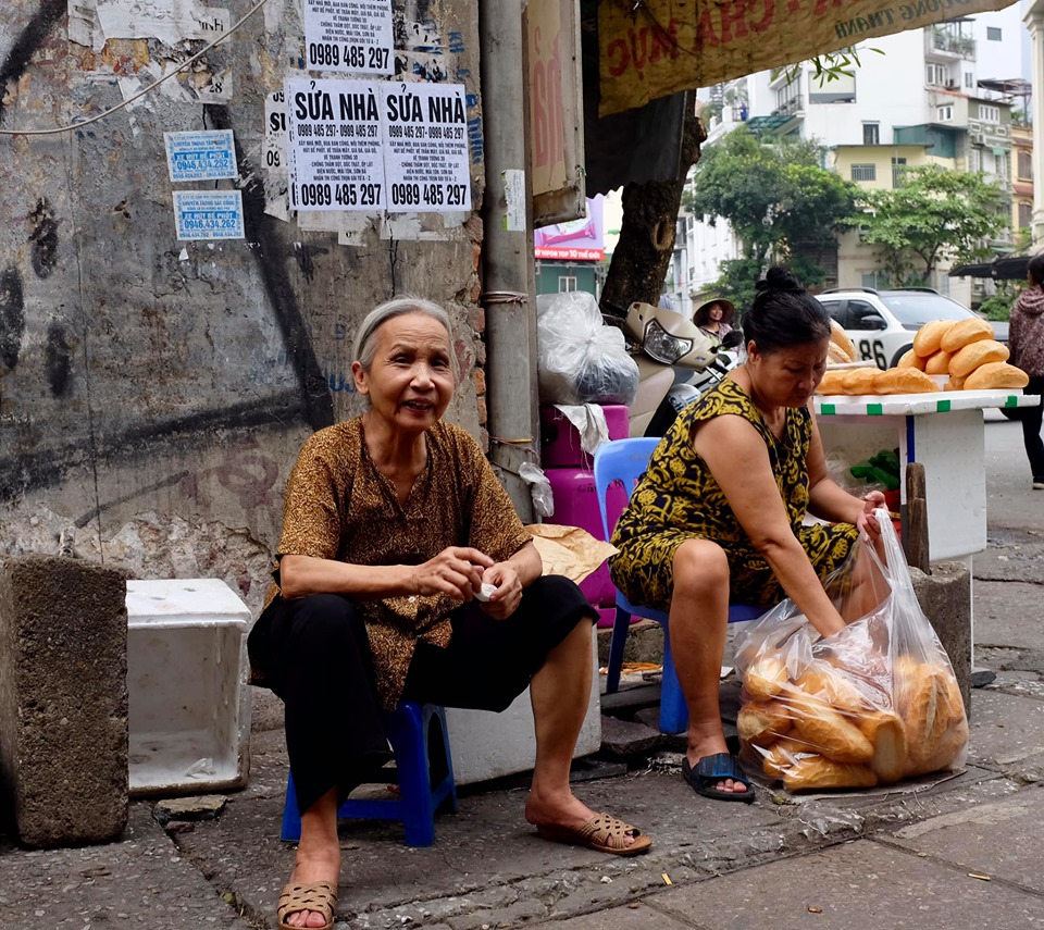 Photo of two ladies sitting on stools in the streets of Hanoi. One is taking bread out of a bag whilst the other smiles at the camera.
