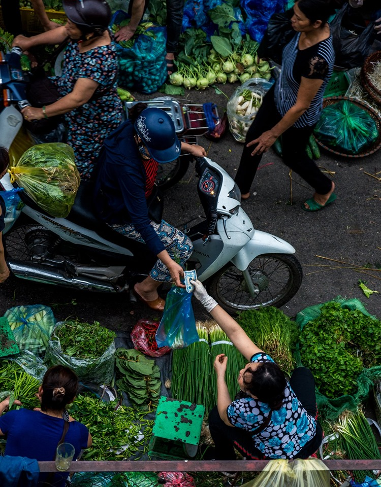 Photo of  a woman on a scooter handing over money whilst collecting a bag of produce
