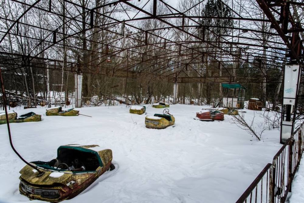 Image of the abandoned dodgems cars in their rusty enclosure.