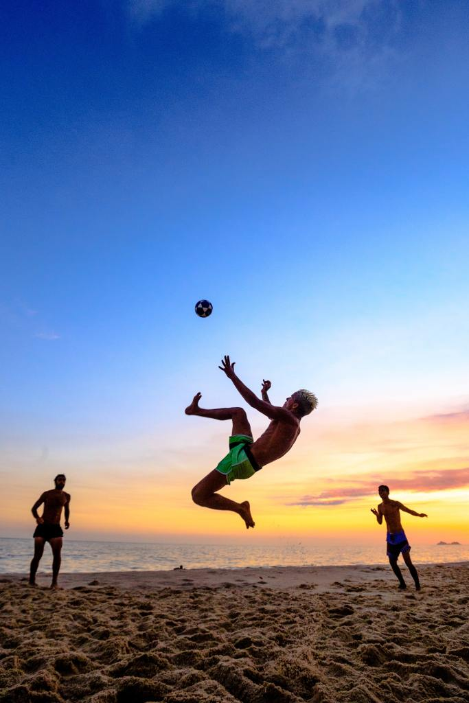 Photo of a man jumping high in the air ready to kick the ball whilst playing football on the beach on Copacabana
