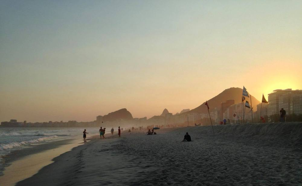 Image of the white sand beach of Copacabana as the sun sets. Despite the depleting light it is still busy with people playing footfall.
