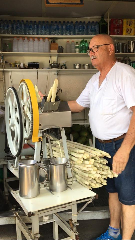 Photo of a man pushing sugar cane through a machine which squeezes out the juice.