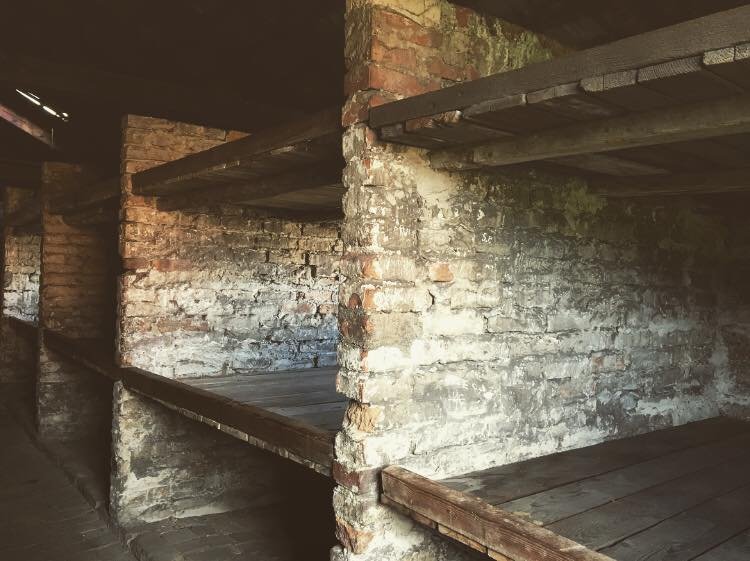 Photo of the sleeping quarters in Auschwitz Birkenau - 3 tier bunk beds.