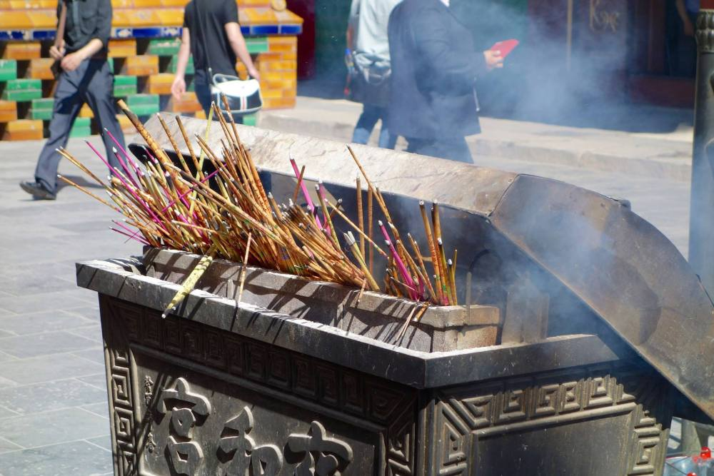 Incense sticks billowing smoke waiting to be picked up ready for prayer