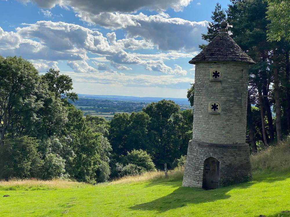 A beautiful tower on a verdant hill with trees surrounding it