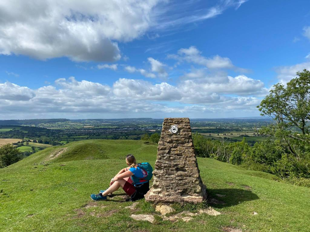 Hares Beacon trigger with Rachel sitting on the ground next to it looking out over Stonehouse