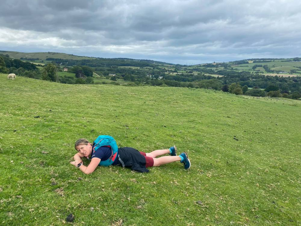 Rachel lying on the ground of yet another hill as we pushed on towards Belas Knap