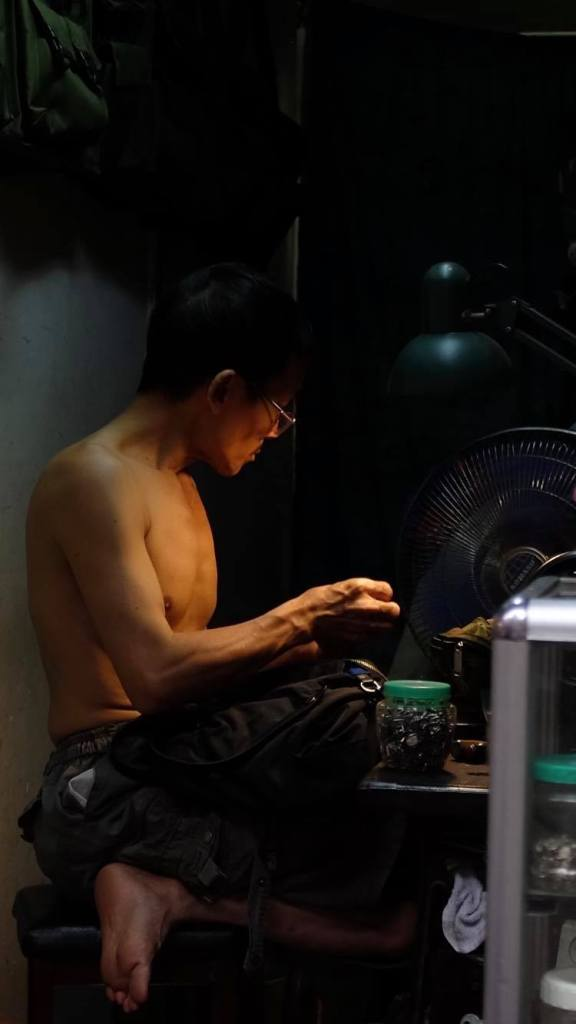 Man sitting in the dark, with just a small amount of light, working on a sweing maching in his workshop