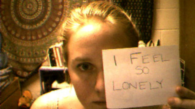 """screencap of Jennifer Ringley looking at her webcam and holding up a note that reads """"I feel so lonely"""""""