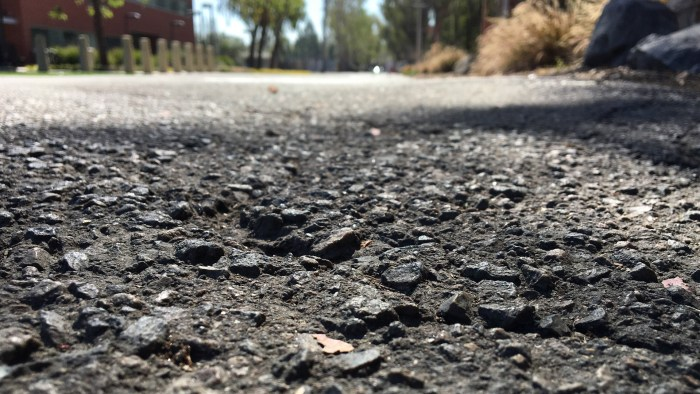 photo of asphalt from a very low angle showing the texture of the asphalt and with buildings and sky in soft focus at the top of the frame