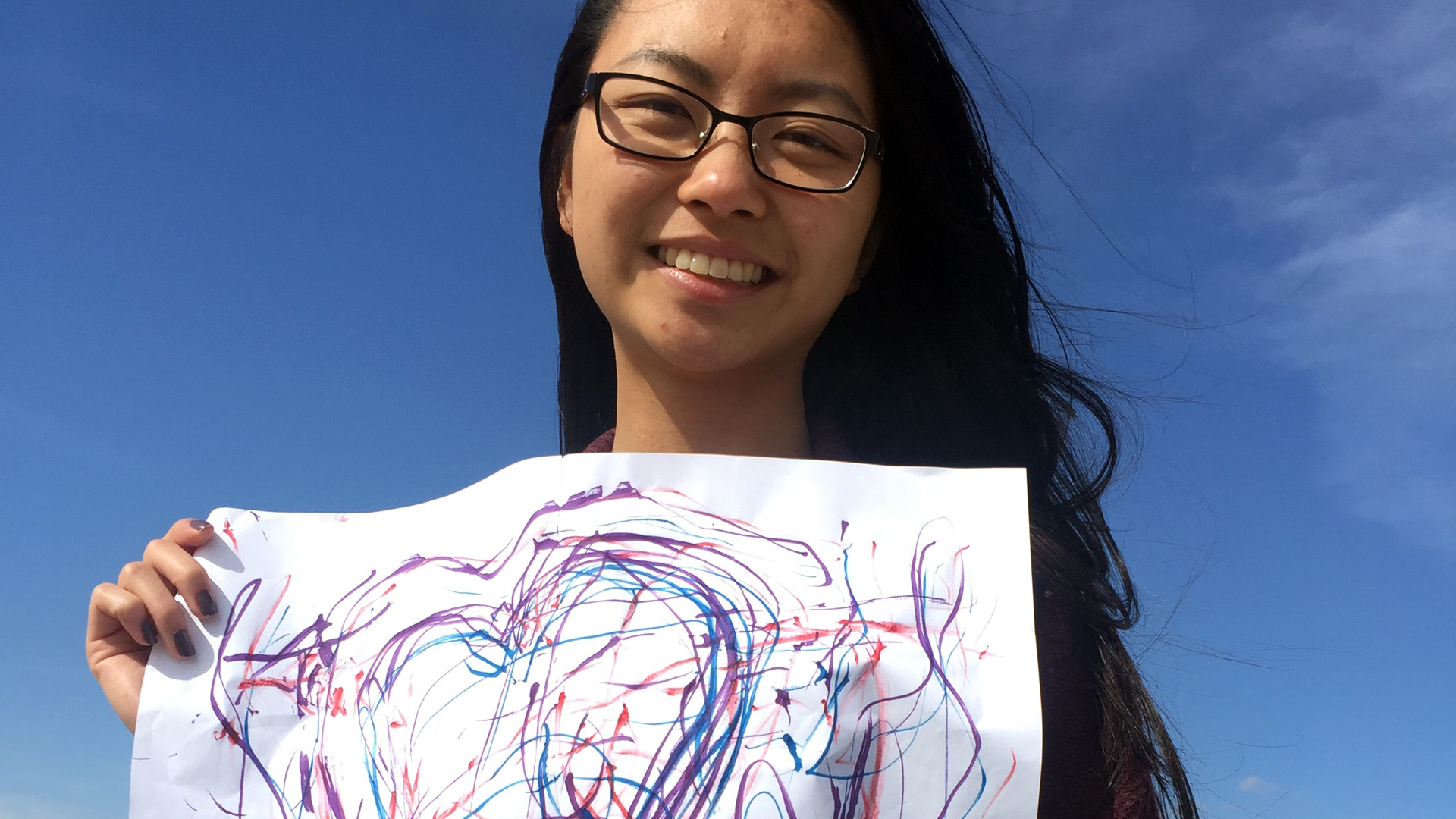 Tiffany Van Gilder holding the results of her Automatic Drawing art experience