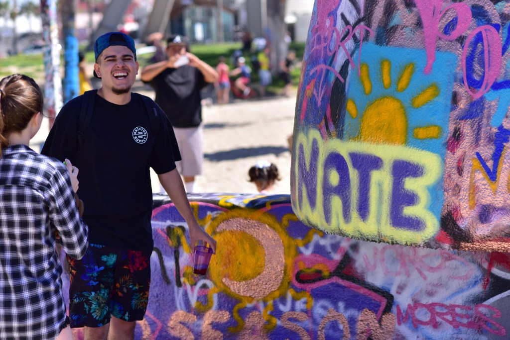 """Nathan Davalos in front of """"Nate"""" painted in yellow and purple on the Venice Art Walls"""