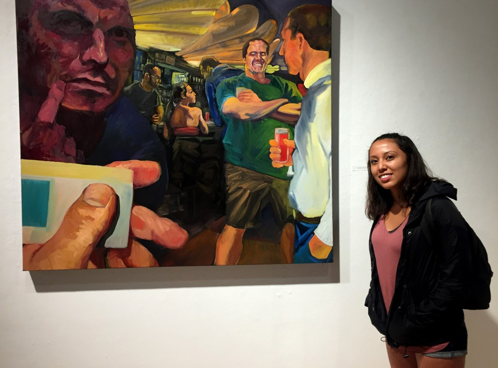Stephanie Archiva in the CSULB Gatov Gallery West with a painting by Andrew Hansen