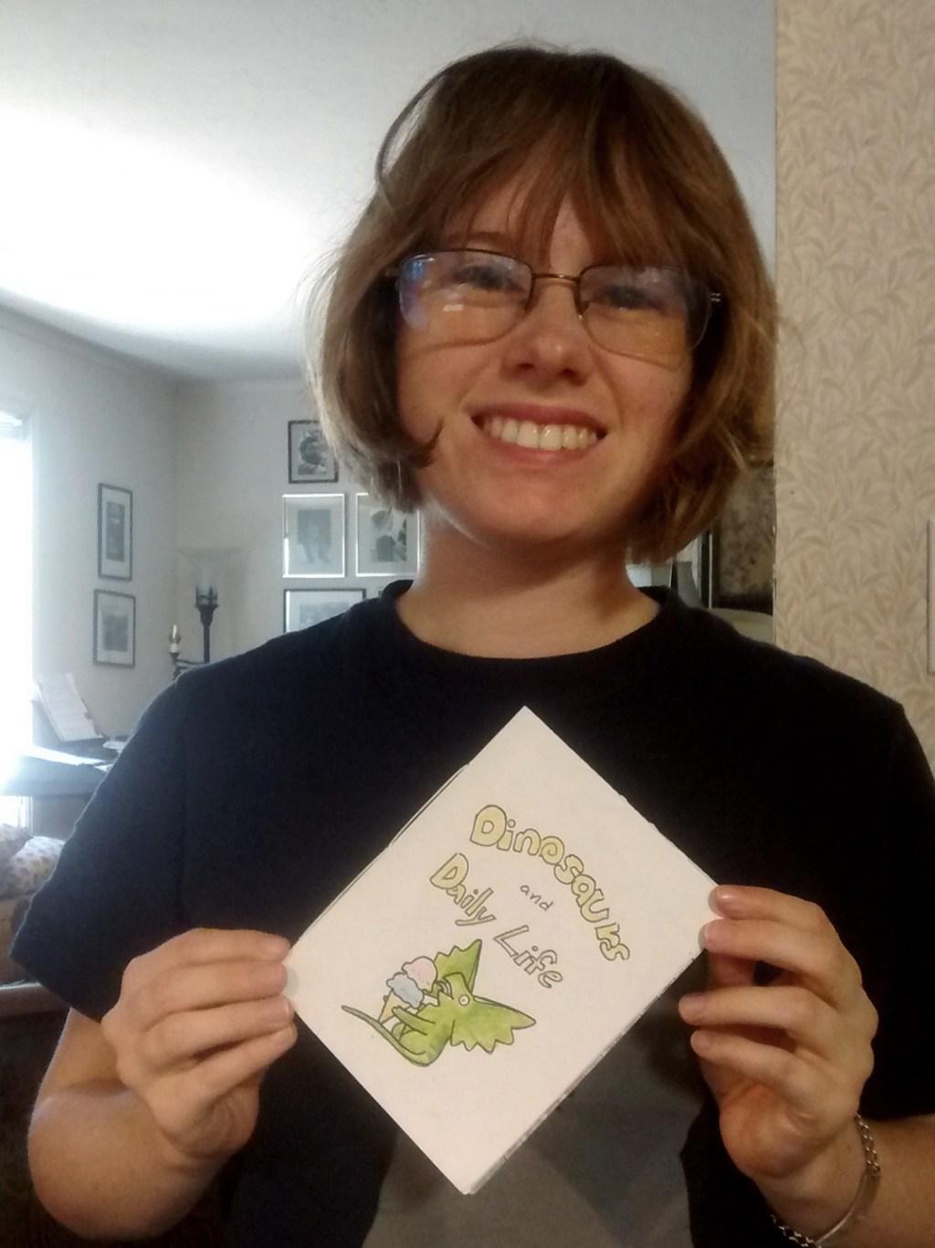 "Hannah Adams holding her zine ""Dinosaurs & Daily Life"""