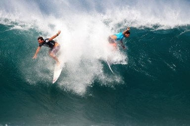 two surfers riding the same wave