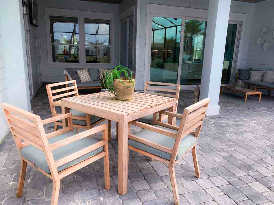 Beach Walk House Tour - Coastal Chic Design and Decor Ideas - Teak dining table with gray blue cushions