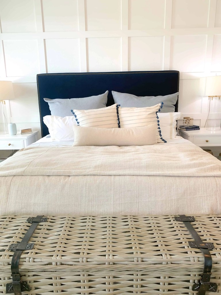 Master bedroom with navy blue upholstered bed frame and coastal neutral bedding