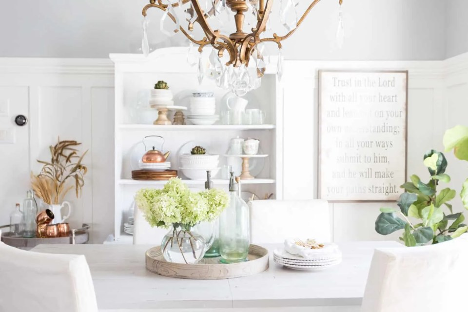 Copper accents in a white dining room.  Coastal blue vases with beautiful flower arrangements on this dining room table.