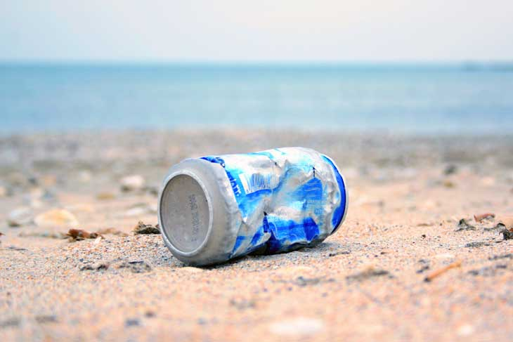 Debris on the beach, marine debris, a crumbled can laying on a secluded beach